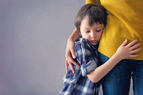 Annesine sarılmış bir çocuk.