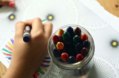 Küçük bir çocuk boya kalemleri ile resim yapıyor