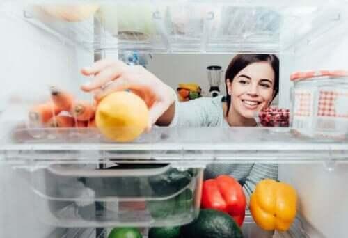 Buzdolabının içinden bir şeyler alan bir kadın.