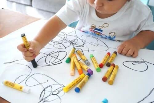küçük çocuk boya kalemleriyle resim yapıyor