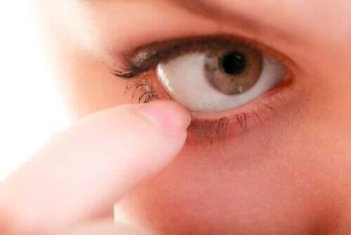 Gözüne dokunan bir kişi.