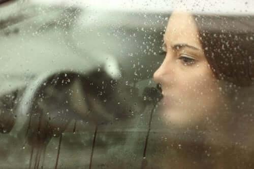 Bir kadın yağmurda buğulanmış ara camından dışarıya bakıyor, üzgün.