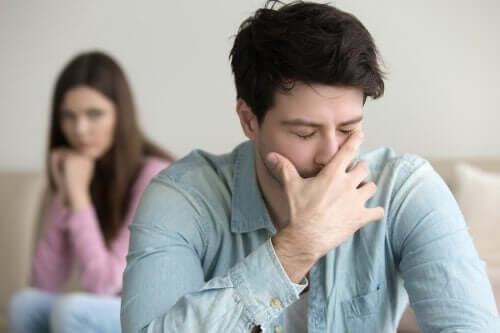Bir erkek önde kızgın ve kadın arkada üzgün ona bakıyor