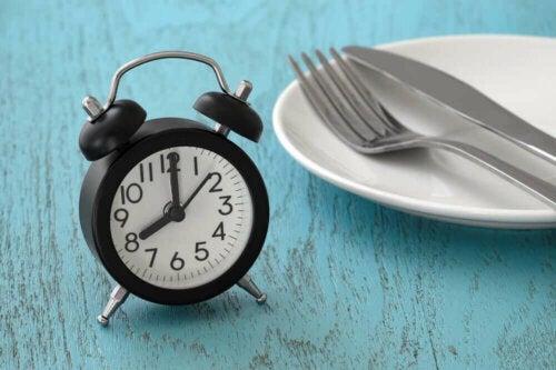 Alarmlı bir saatin yanında duran tabak, çatal ve bıçak.