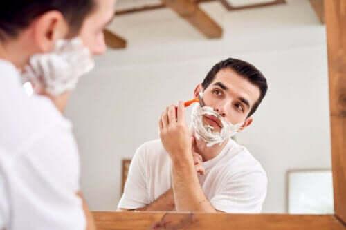 Aynaya bakarak tıraş olan bir adam.