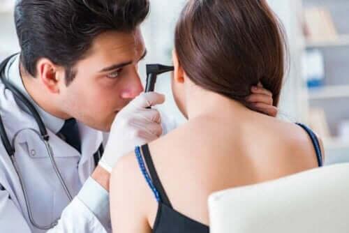 Bir kadının kulağını kontrol eden bir doktor.