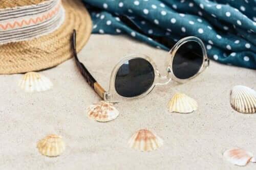 Kumsalda güneş gözlüğü ve şapka