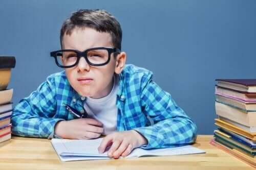 gözlerini kısmış ders çalışan gözlüklü çocuk
