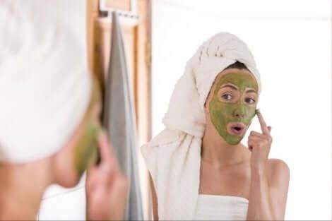 Kadın aynada yüzüne maske yapıyor