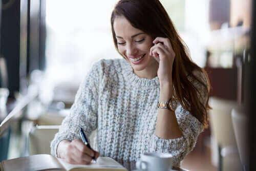 Önündeki deftere bir şeyler yazan mutlu bir kadın.