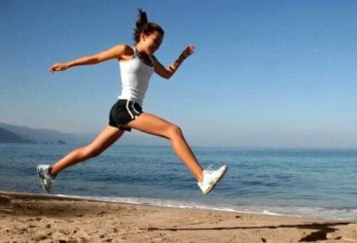 Sahilde koşu yapan bir kadın.