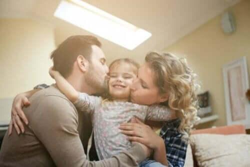 Çocuklarını öpen bir anne-baba.
