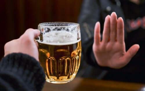 Bir bardak bira uzatılıyor ve karşı taraf eliyle reddediyor