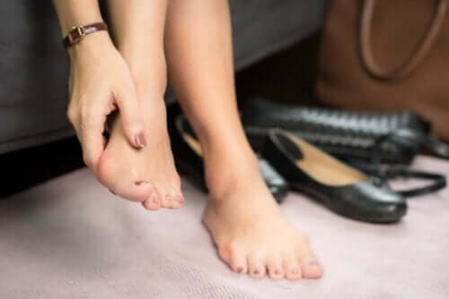 Ayağına masaj yapan bir kadın.
