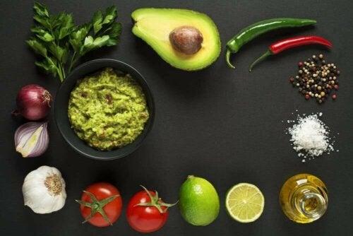 Bir kase guacamole ve guacamole yapmak için kullanılan malzemeler.
