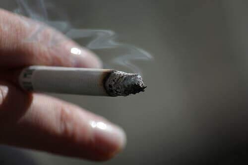 Elinde sigara tutan bir kişi.