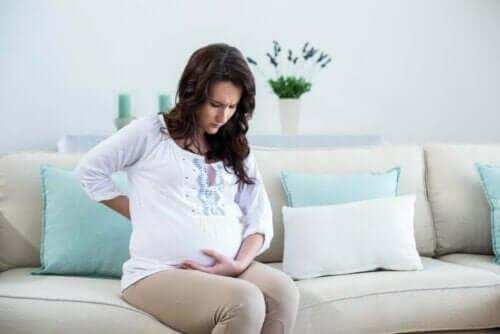 Sırtı ağrıyan hamile bir kadın.