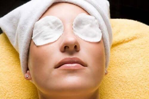 Gözlerine soğuk kompres yapan bir kadın.