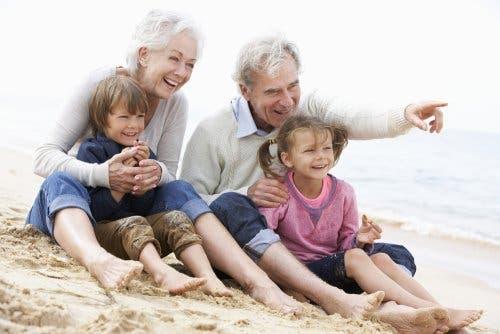 Torunlarıyla plajda oturan bir büyükanne ve büyükbaba.