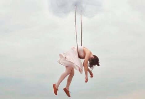 Bir kadın havada salıncakta baş aşağı duruyor.