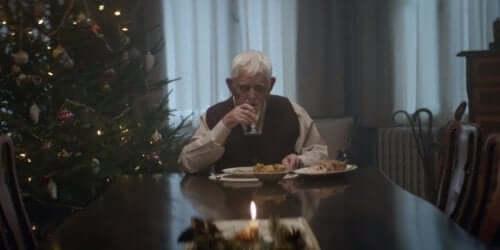 yemek masasında oturan ve su içen adam