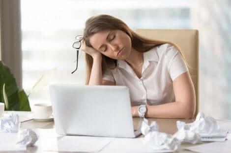 Yorgun bir kadın bilgisayar başında oturuyor