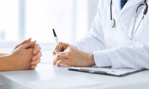 Hastasının tıbbi öyküsünü almakta olan bir doktor.