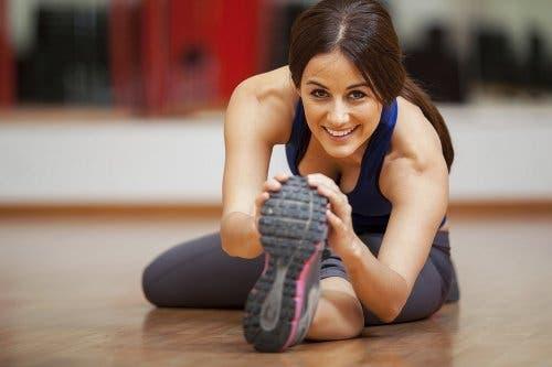 Varisli damarları rahatlatmak için esneme egzersizleri yapan bir kadın.