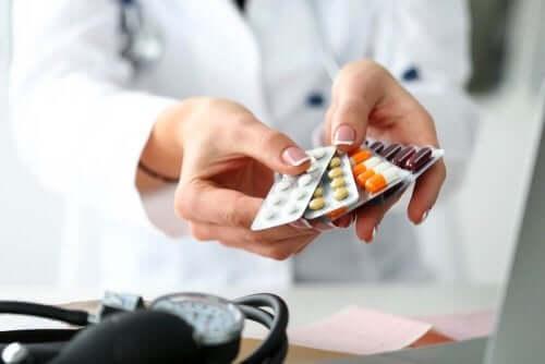 Elinde çeşitli ilaçlar tutan bir kişi.