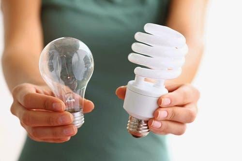 Evindeki eski ampulleri LED ampuller ile değiştiren bir kişi.