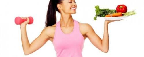 Bir elinde ağırlık bir elinde sebze tabağı olan kadın