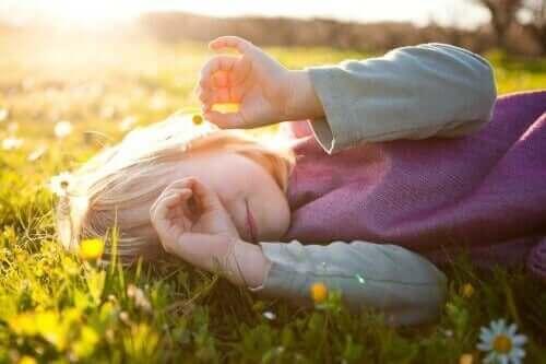 Çiçeklerin üzerine uzanmış eliyle dürbün yapan kız