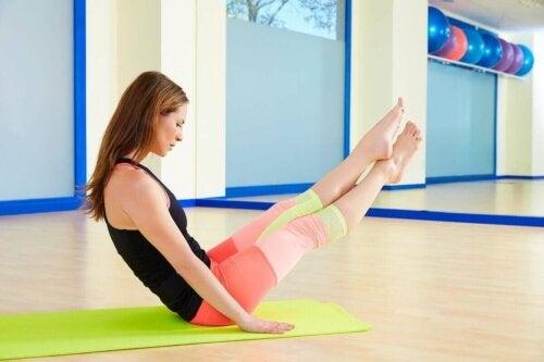 Bumerang adlı pilates egzersizini yapan bir kadın.