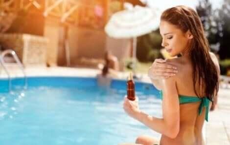 Havuz başında güneş kremi süren kadın