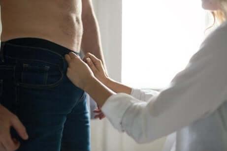 erkeğin pantolonunu açan kadın