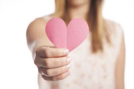 Elinde kalp figürü tutan kadın
