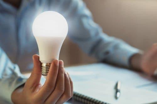 Elinde LED ampul tutan bir kişi.