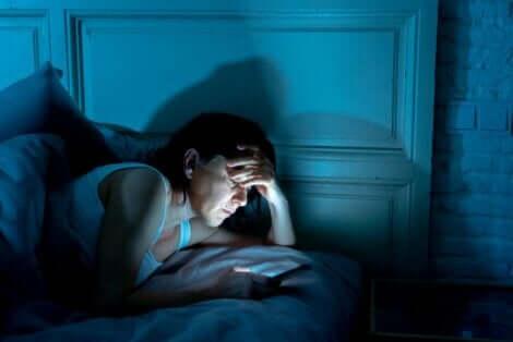 Yatmadan önce telefonda vakit geçiren kadın