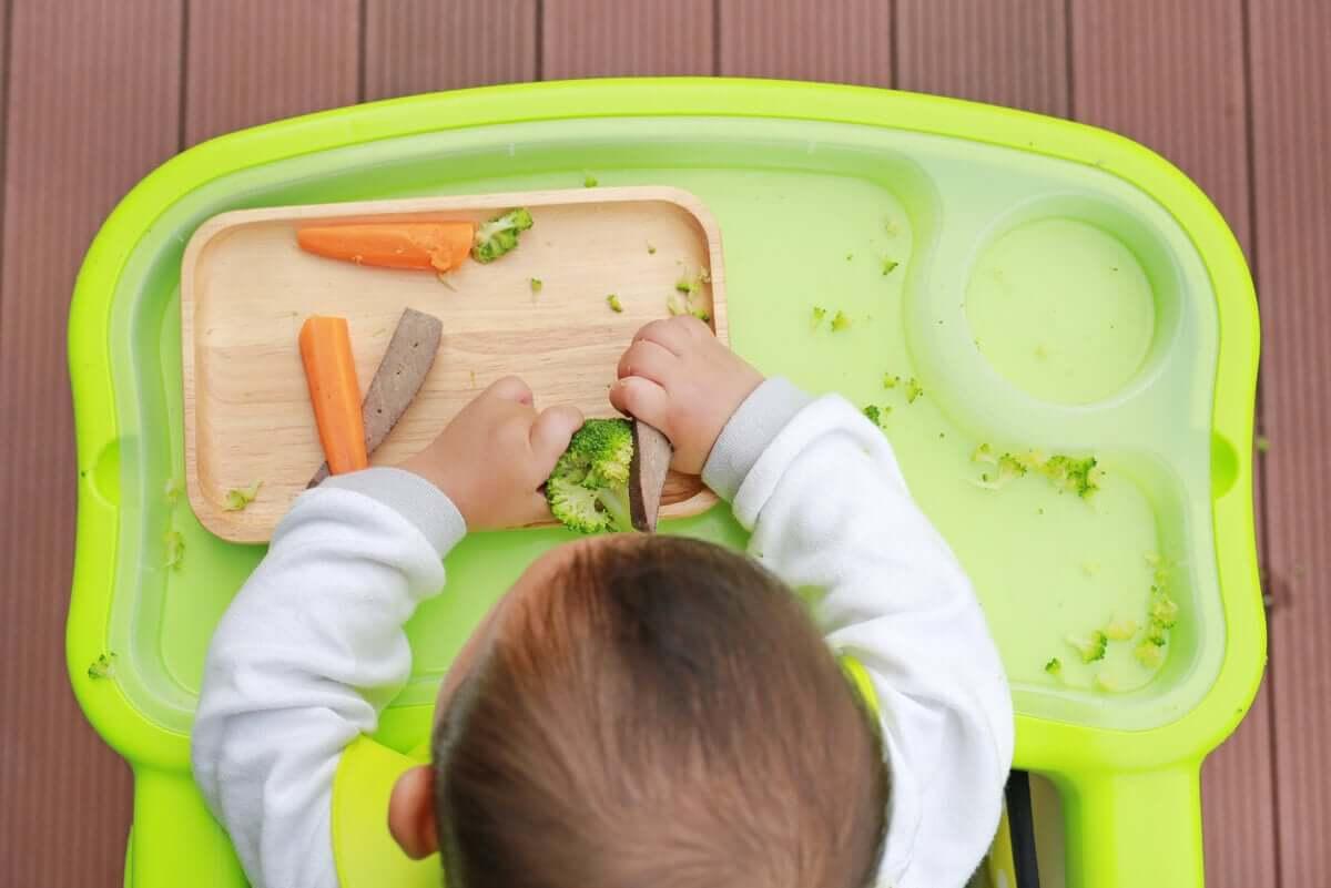 yemek yerken oynayan bir bebek