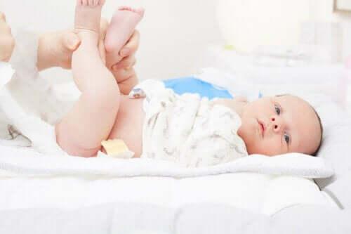 Bir kişi bebeğin bezini değiştiriyor