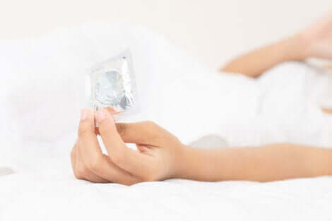 Prezervatif paketi tutan kadın
