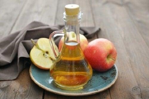 Bir şişe elma sirkesi ve yanındaki elmalar.