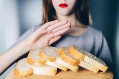 Bir kadının önünde ekmek dilimleri duruyor kadın elleriyle ekmeklerin önünü kapatıyor