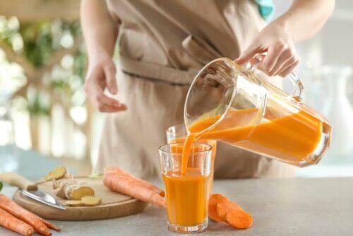 Sürahiden bardağa havuçlu smoothie döken bir kadın.