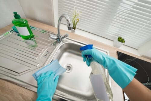 Paslanmaz çelik bir lavaboyu temizleyen bir kişi.