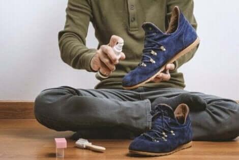 Süet ayakkabıya sprey sıkan adam