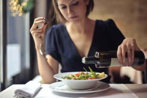 bir kadın salatasına zeytinyağı döküyor