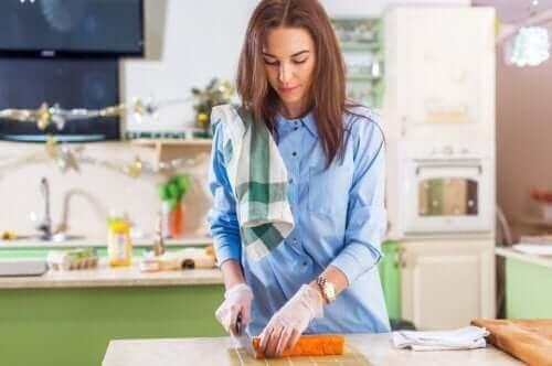 elinde eldivenle yiyecek doğrayan kadın