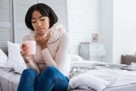 Ballı çay içerek boğaz ağrısı ile savaşan kadın
