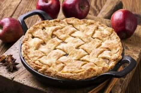 masanın üzerinde pişmiş bir turta ve birkaç elma duruyor
